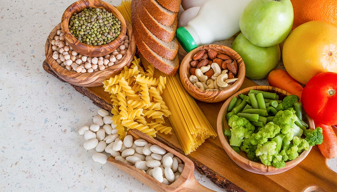 A collection of healthy food, including beans and chickpeas, spread out on a table
